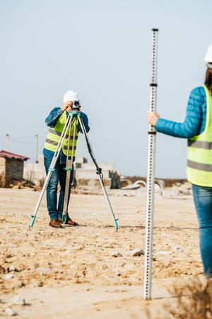 Selective focus of surveyors working with ruler and digital level on construction site