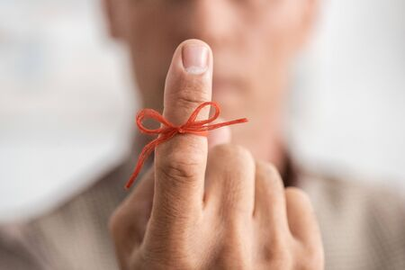 selective focus of red bow on finger of senior man with mental illness Archivio Fotografico