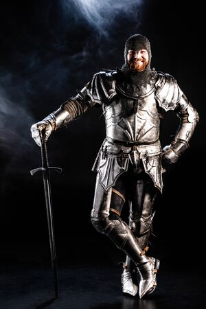 smiling knight in armor looking at camera and holding sword on black background