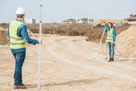 Topógrafos con nivel digital y regla topográfica trabajando en camino de tierra