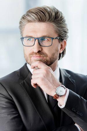 pensive diplomat in glasses touching face in embassy Standard-Bild