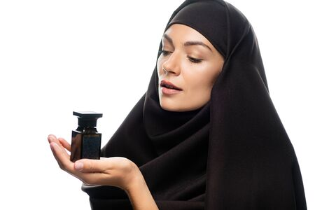 young Muslim woman in hijab holding bottle of perfume isolated on white Stock Photo - 134633525