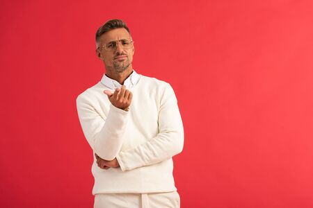 handsome man in glasses gesturing isolated on red