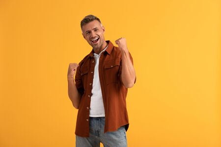 excited man with clenched fists isolated on orange Stock Photo