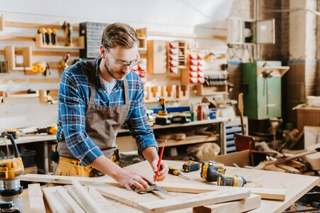 handsome carpenter in goggles holding pencil in carpentry shop