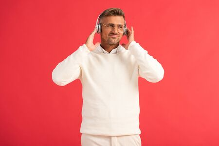 displeased man listening music in wireless headphones isolated on red