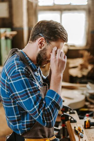 carpenter covering face while touching googles in workshop Stock Photo