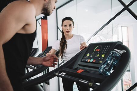 attentive trainer looking at sportsman running on treadmill Stock Photo