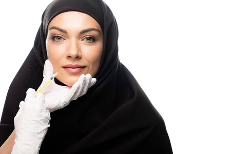 young Muslim woman in hijab having beauty injection isolated on white, lip augmentation concept
