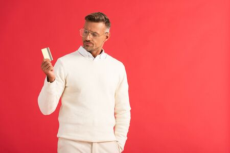 stylish man in glasses holding credit card isolated on red Reklamní fotografie