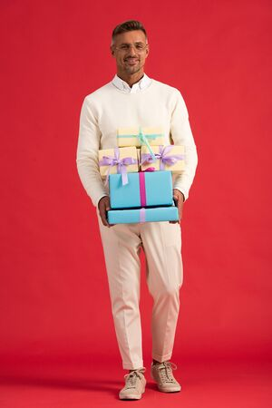happy man in glasses holding gift boxes while standing on red Reklamní fotografie