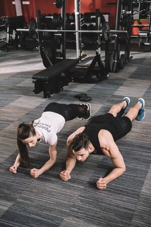 young trainer doing plank exercise together with sportsman Stock Photo