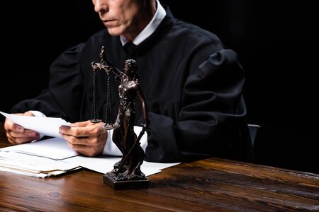cropped view of judge in judicial robe sitting at table and reading paper isolated on black