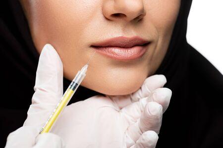 Vista recortada de la joven musulmana en hijab con inyección de belleza aislado en blanco, concepto de aumento de labios