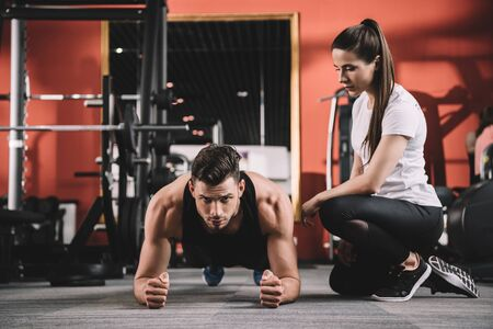 attentive trainer supervising handsome sportsman doing plank exercise Stock Photo