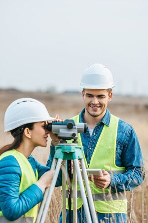 Smiling surveyors working with digital level and tablet in field