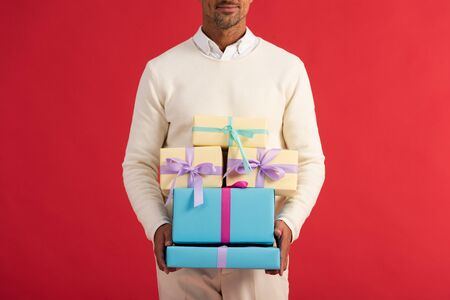 cropped view of happy man holding gift boxes isolated on red Reklamní fotografie