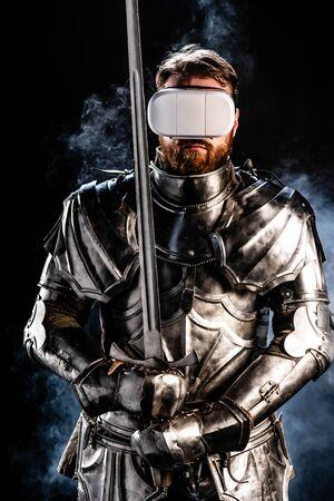 Ritter mit Virtual-Reality-Headset in Rüstung mit Schwert auf schwarzem Hintergrund Standard-Bild