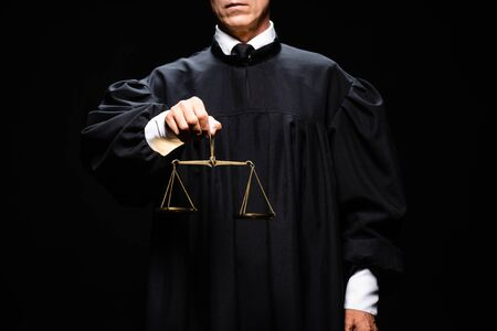 cropped view of judge in judicial robe holding scales of justice isolated on black