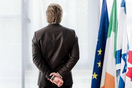 Rückansicht des Diplomaten, der mit geballten Händen in der Nähe von Flaggen steht Standard-Bild