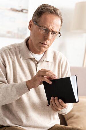 senior man with alzheimer disease holding notebook at home Foto de archivo - 134634400