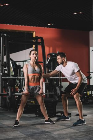 handsome trainer supporting attractive sportswoman lifting barbell