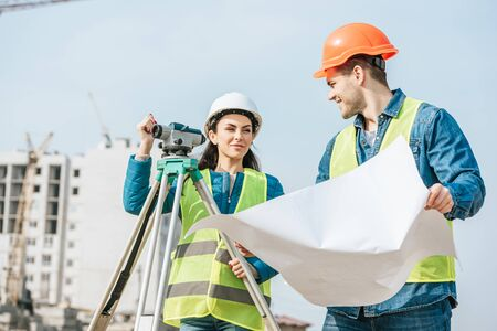 Smiling Surveyors with blueprint and digital level