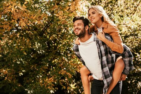 happy young man piggybacking happy girlfriend in park