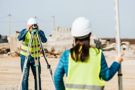 Selective focus of surveyors with digital level and survey ruler on construction site