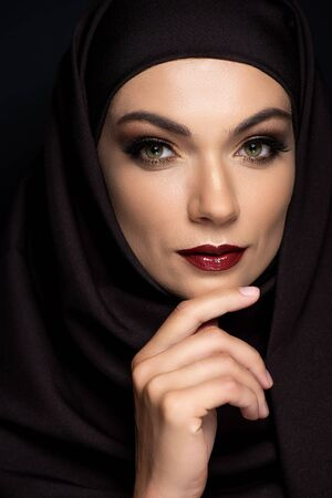 young Muslim woman in hijab with smoky eyes and red lips isolated on black Stock fotó