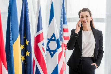 attractive diplomat standing with hand in pocket and talking on smartphone near flags