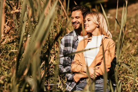 selective focus of happy young man embracing smiling girlfriend in thicket of sedge