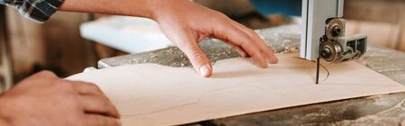 panoramic shot of woodworker using cnc machine in workshop