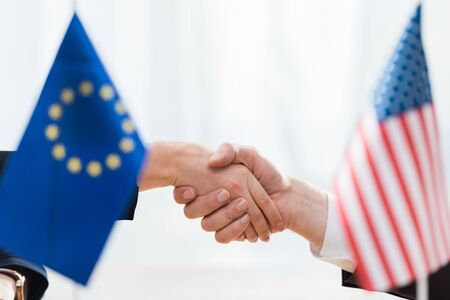 selective focus of diplomats shaking hands near flags of usa and european union