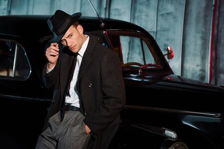stylish man touching hat while standing with hand in pocket near retro car Reklamní fotografie