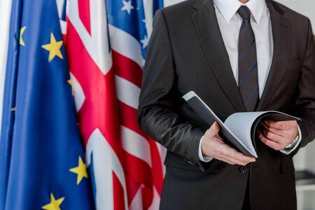 cropped view of diplomat holding folder near flags Standard-Bild