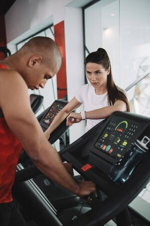 attentive trainer in fitness tracker looking at african american sportsman running on treadmill
