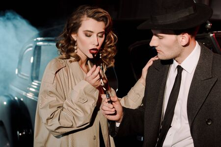 handsome gangster in hat holding lighter near attractive woman smoking near car on black with smoke