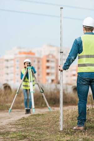 Selective focus of surveyors measuring land with digital level and ruler