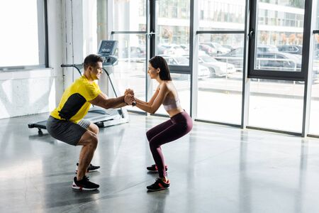 side view of sportsman and sportswoman doing squat together in sports center