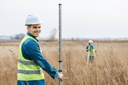 Selective focus of smiling surveyor with ruler and colleague with digital level in field