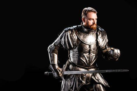 Schöner Ritter in Rüstung mit Schwert isoliert auf Schwarz