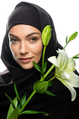 young Muslim woman in hijab holding lily isolated on white
