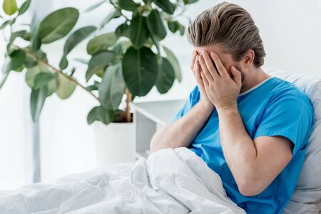 sad patient in medical gown sitting on bed and crying in hospital Stockfoto