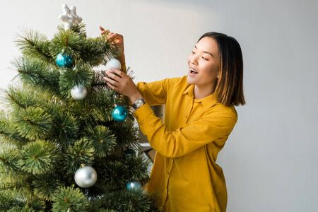 excited asian woman decorating christmas tree in office Imagens