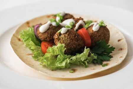 close up view of falafel with sauce on pita with vegetables in white plate Reklamní fotografie