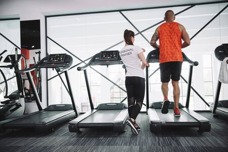 back view of personal trainer supervising african american sportsman running on treadmill