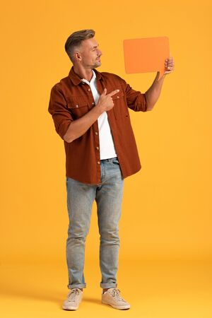 happy man pointing with finger at speech bubble on orange