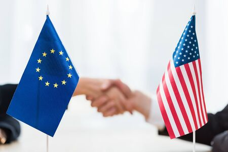 selective focus of flags of usa and european union near diplomats shaking hands Фото со стока
