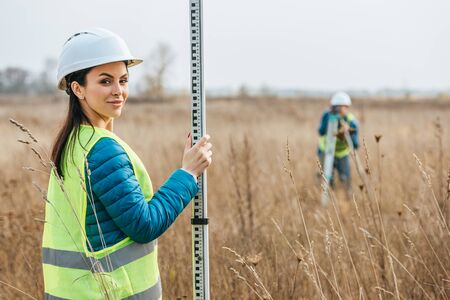 Selective focus of female surveyor with ruler and colleague with digital level in field